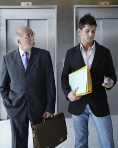 Old-businessman-looking-at-young-worker