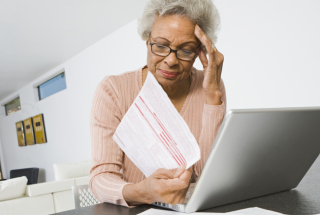 Elderly_woman_paperwork_ss_121893061